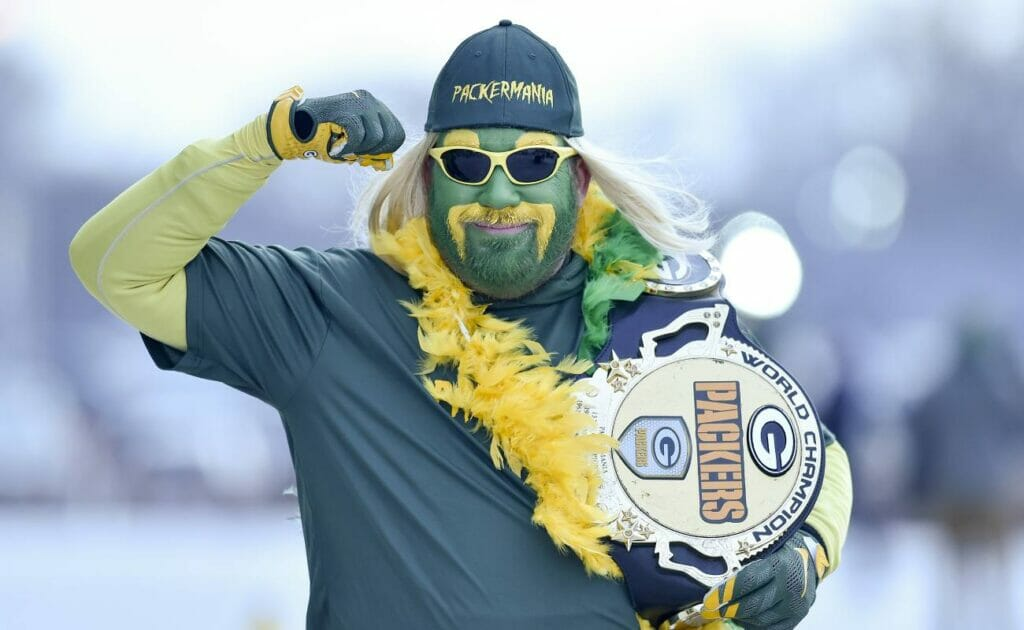 A fan of the Green Bay Packers flexes his right arm while carrying a Green Bay Packers belt in his left. Photo by Quinn Harris/Getty Images.