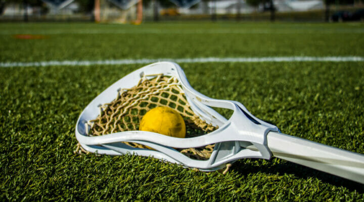 Yellow ball and lacrosse stick lying on a green playing field.