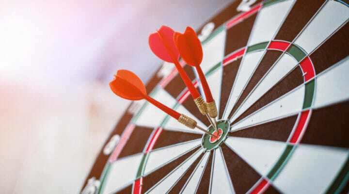 Close-up of a dartboard with bullseye darts against a blurred background.