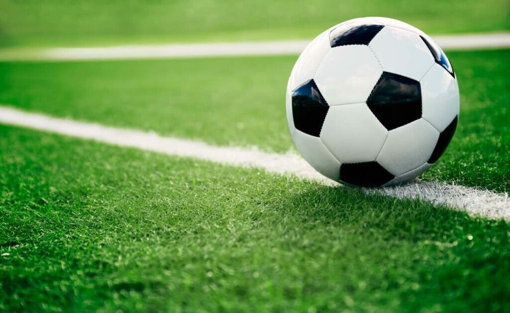Traditional black-and-white soccer ball on a field.