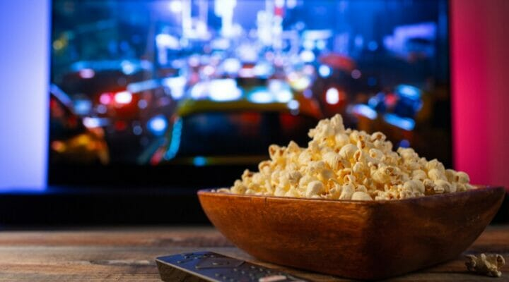 A bowl of popcorn sits on a table in front of a TV.