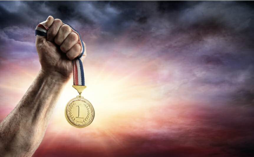 A person holding up a gold medal with the number 1 on it.