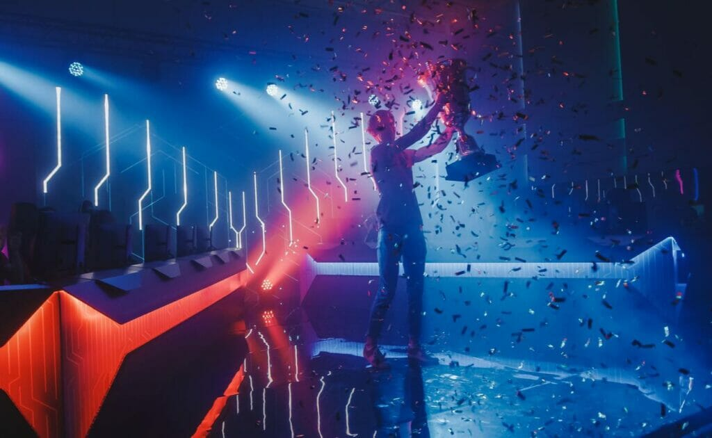 Illustration of an eSports winner standing on a neon-lit stage, holding a trophy while surrounded by confetti.
