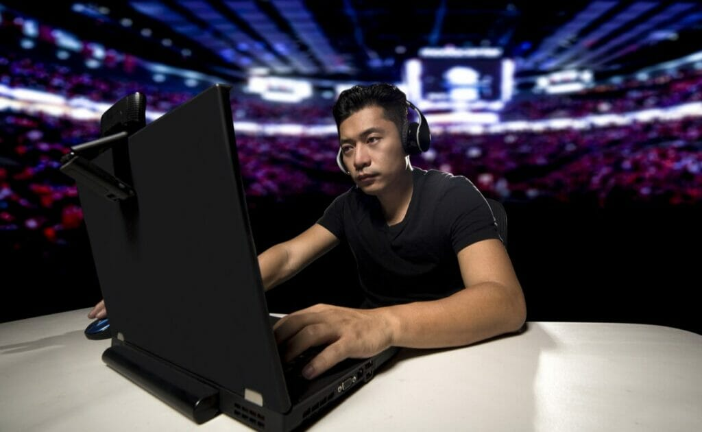 Professional eSports video gamer playing an FPS or MMO game on a computer and streaming online.