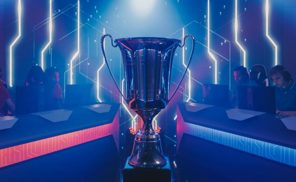 Two eSports teams competing for a trophy in a neon-lit room.