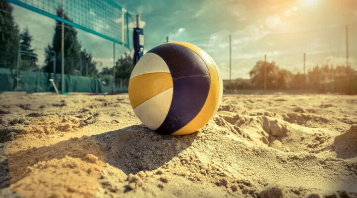 A volleyball in the sand as the sun sets.