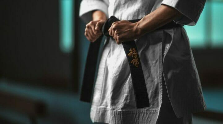 A woman tightening her karate belt.