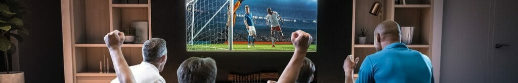 A group of friends watching a soccer match on TV in the living room.