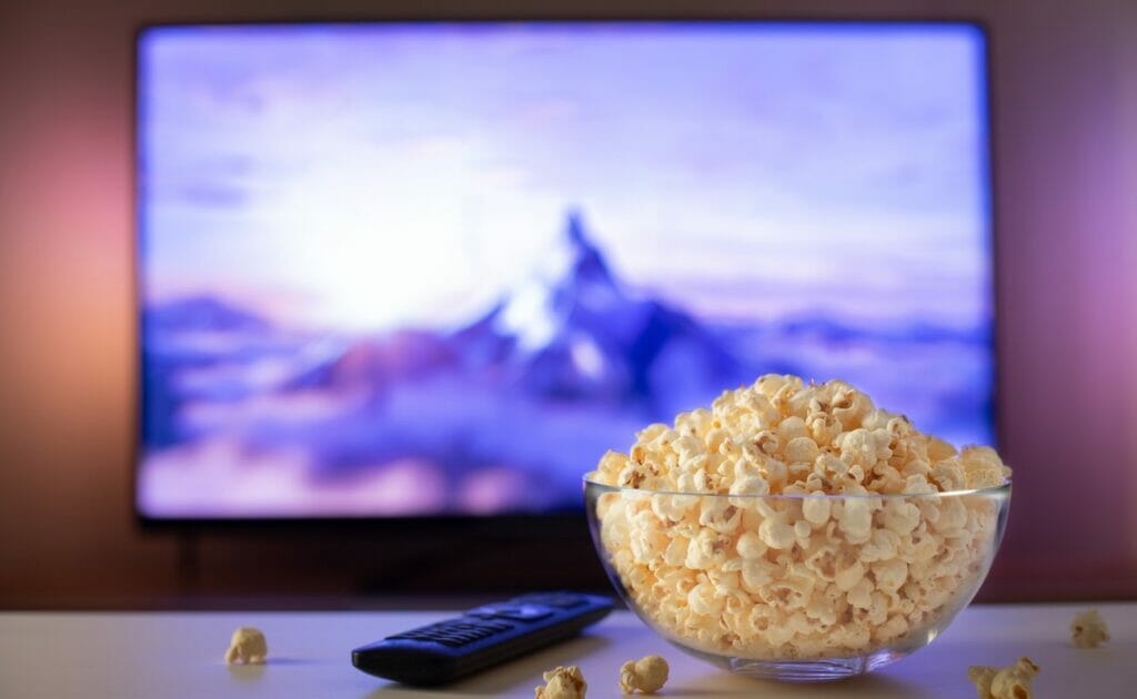 A bowl of popcorn on a coffee table with a movie on the TV screen in the background.