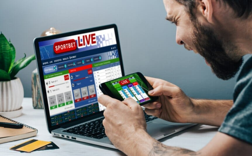A man watches the sports results on his phone and laptop.
