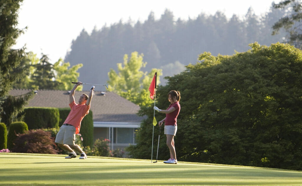A woman holding the flag on the green while a man celebrates with his club and hands in the air