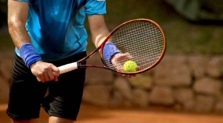 A man prepares to serve during a tennis match.