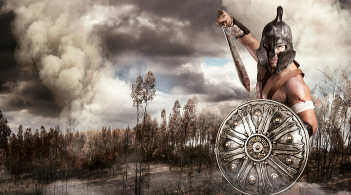 A gladiator with a helmet and a sword with dark clouds in the background.