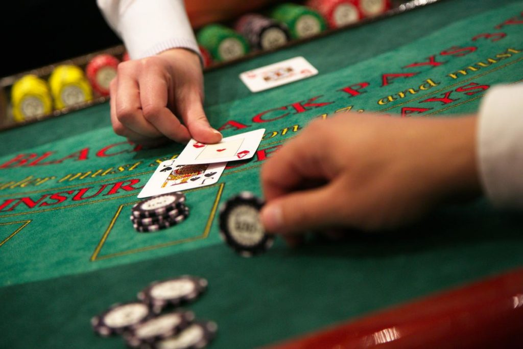 Dealer hands out 2 cards to a player who is placing chips on the green table