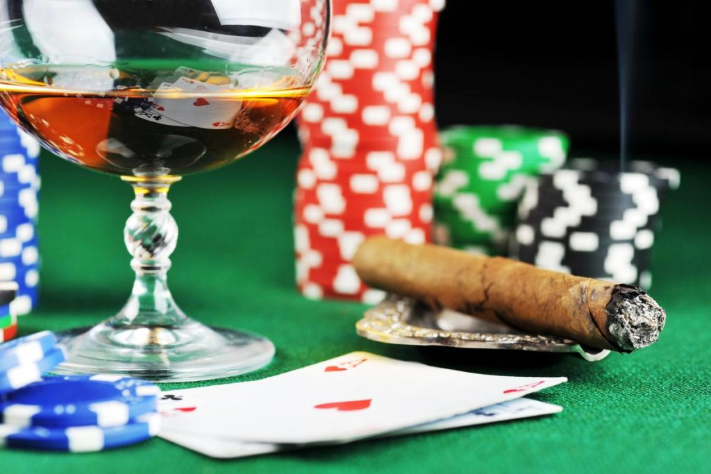 Cigar, poker chips, whiskey glass and playing cards on a green casino table