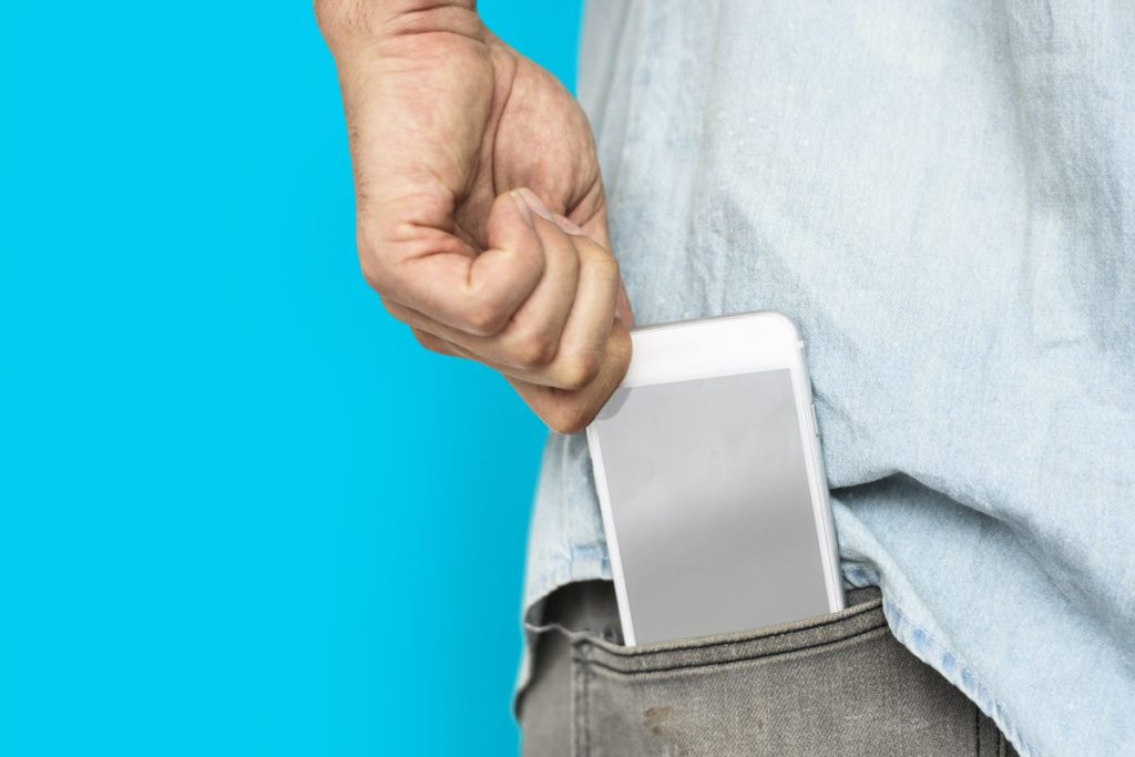 Man placing his phone in his back jeans pocket, with an aqua blue background