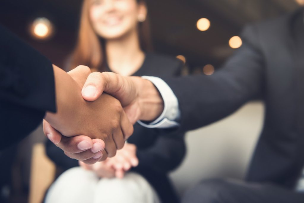 2 people wearing suits shaking hands as a sign of etiquette