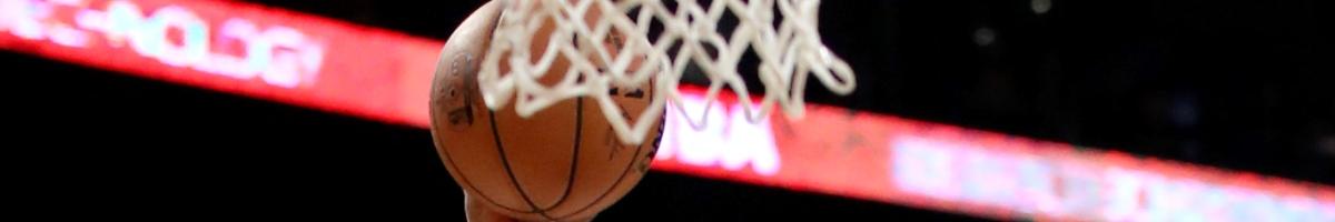 Hand on basketball thrown behind basketball net