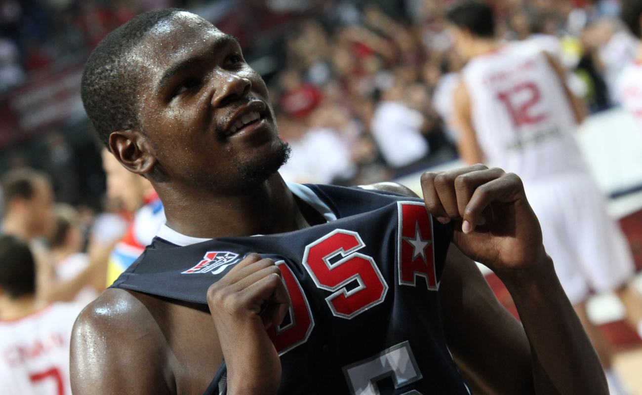 Kevin Durant holding his USA basketball jersey and smiling