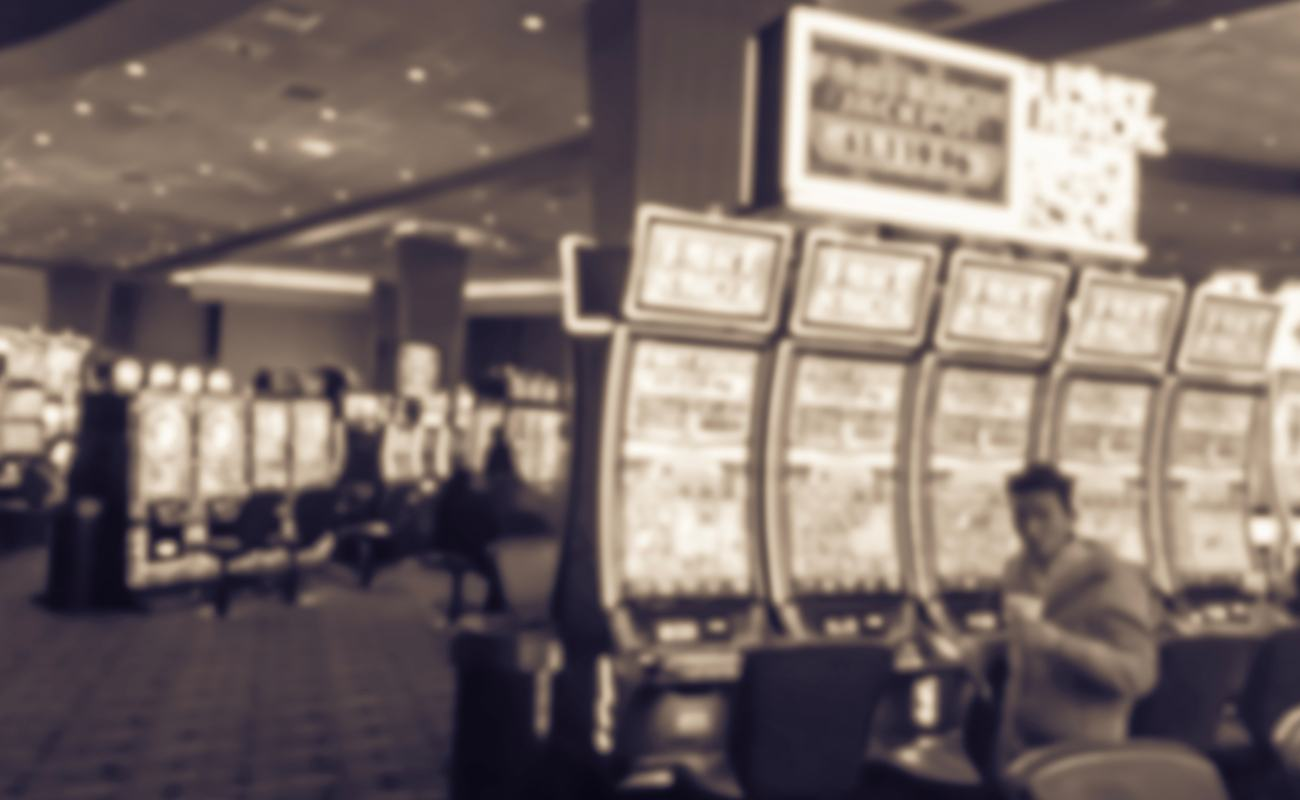 sepia blurred image of slot machines in vintage casino