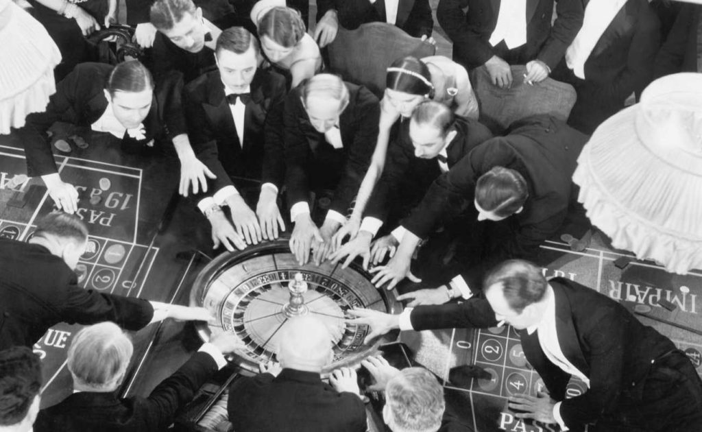 vintage black and white photo of men crowding around a roulette wheel