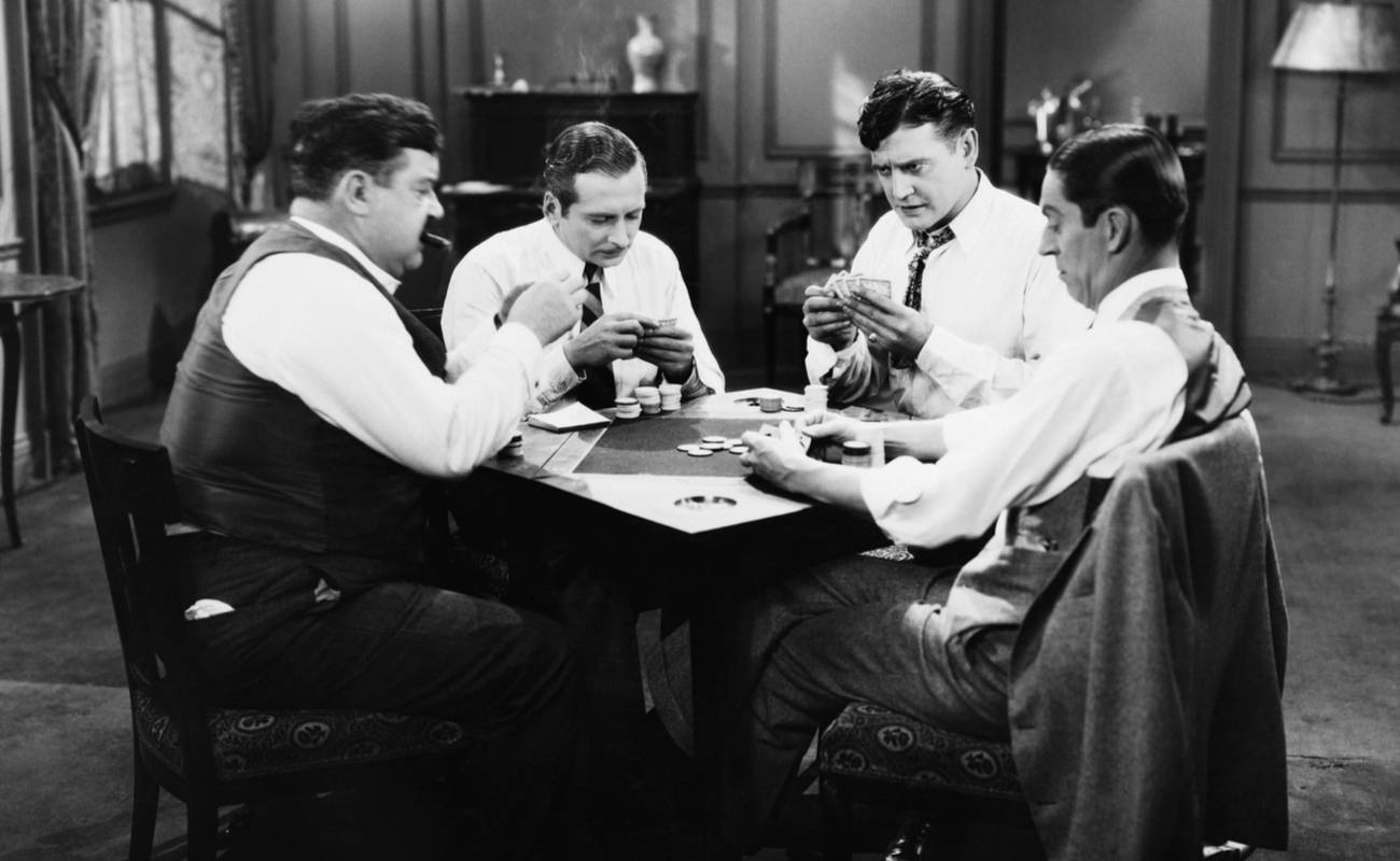 black and white photo of group of men playing poker around a table