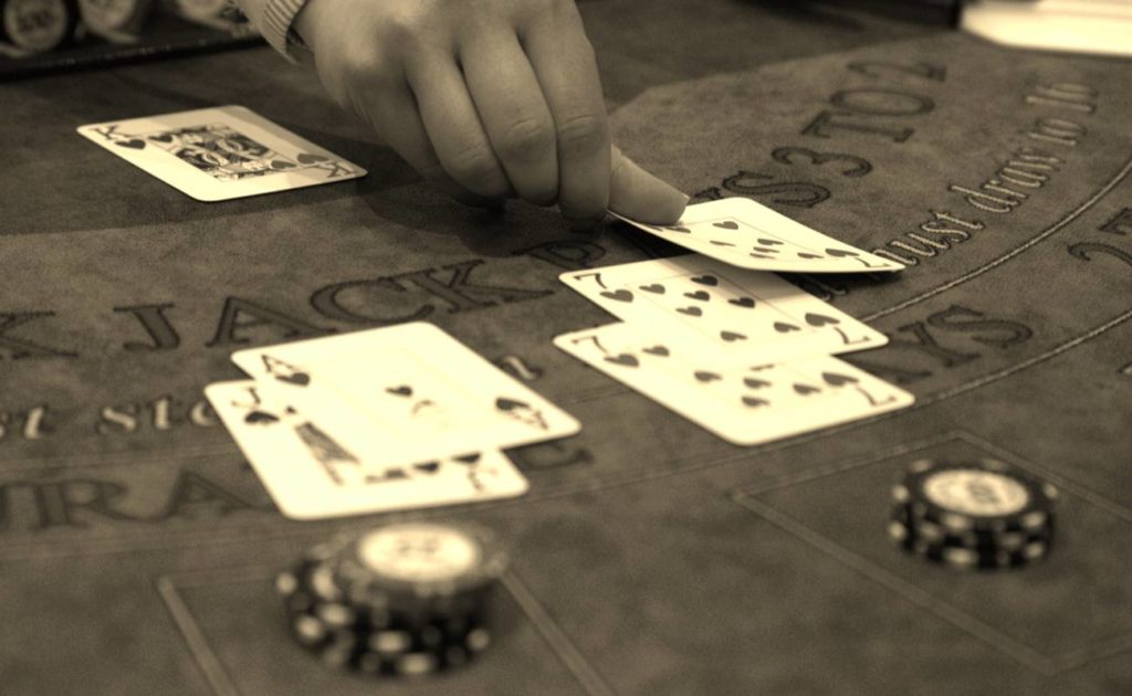sepia photo of man dealing cards during game of blackjack