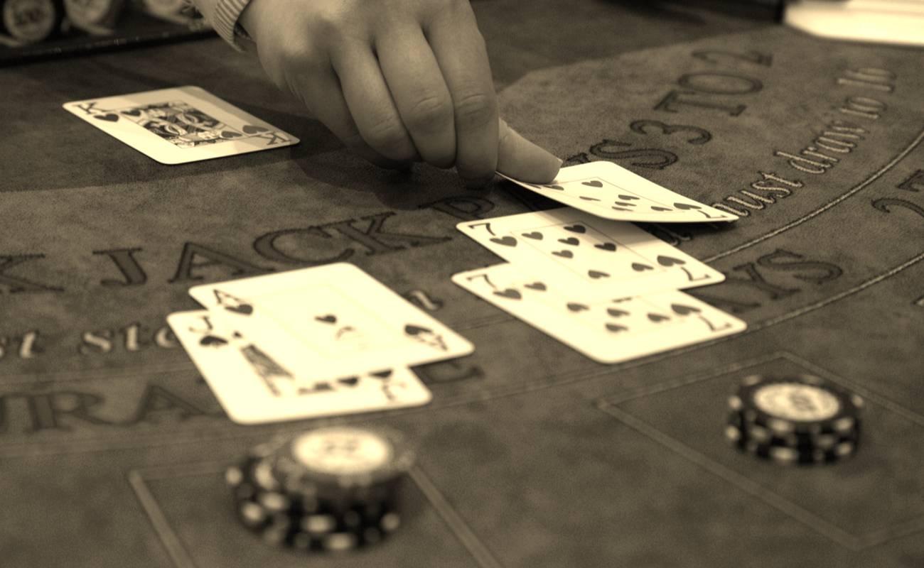 sepia photo of man dealing cards during game of blackjack