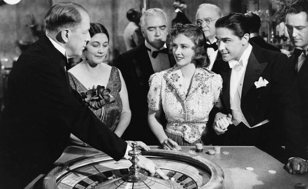 black and white photo of vintage casino with people at roulette table