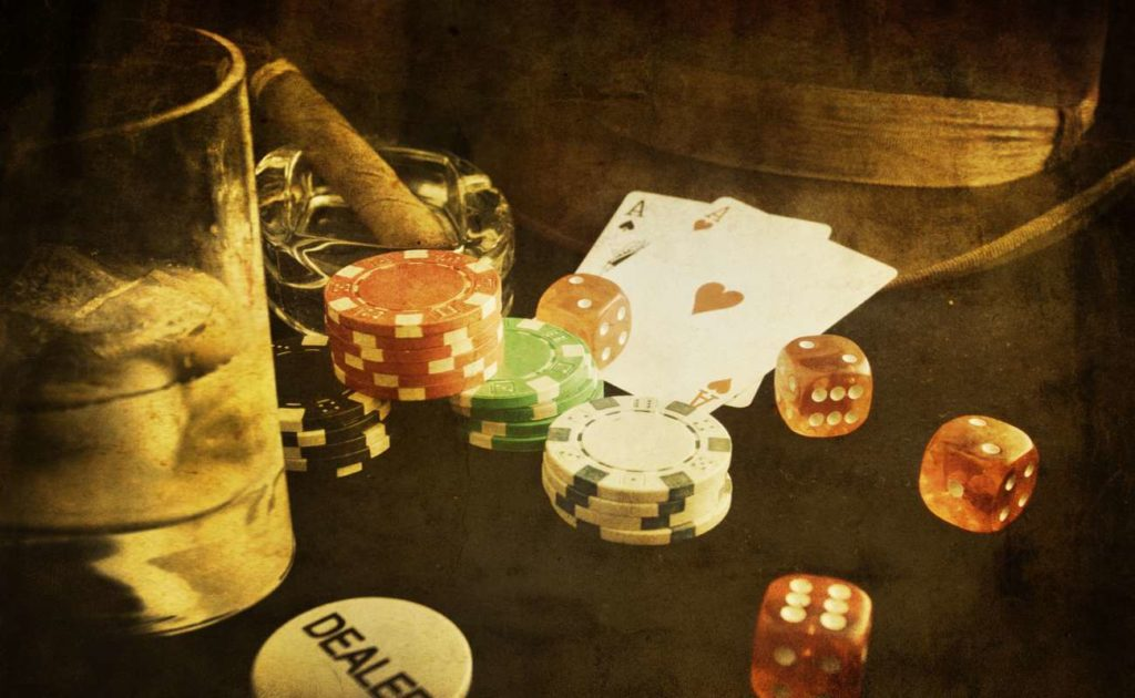 vintage photograph of poker chips and playing cards next to glass of whisky