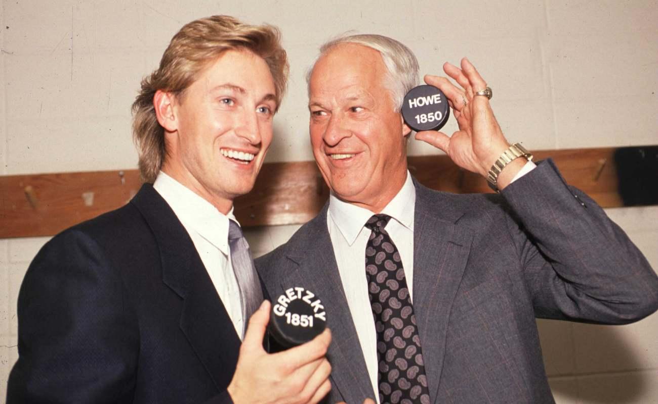 Gordie Howe and Wayne Gretzky with pucks in their hand