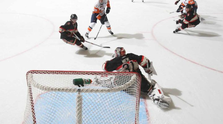 Hockey player scoring a goal while goalie tries to stop the puck
