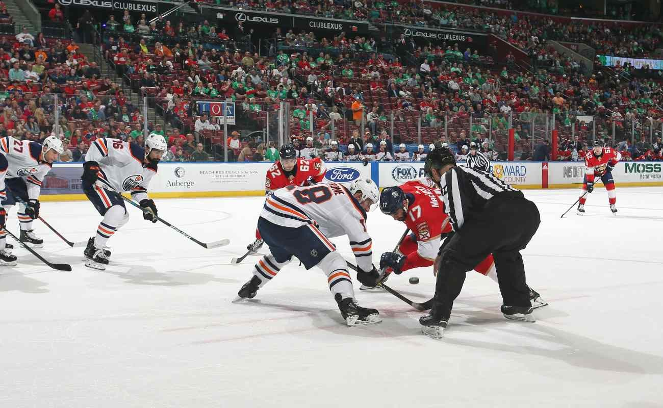 Edmonton Oilers vs Florida Panthers, players reaching for the puck with the referee watching on