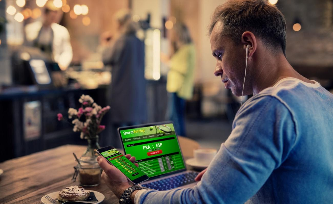 A man in a cafe looking at sports betting results on his laptop and smartphone