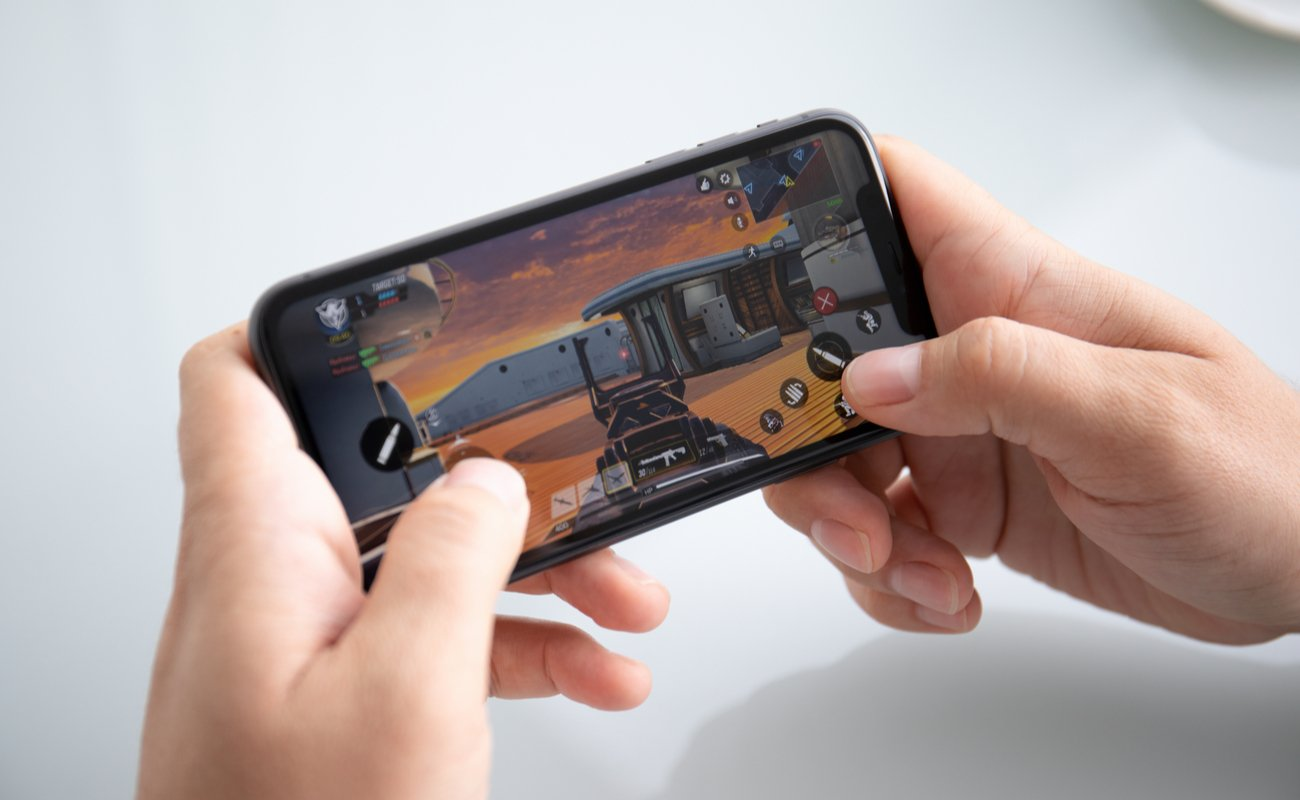 Pair of hands holding an iPhone in portrait mode playing Call of Duty with a white background.