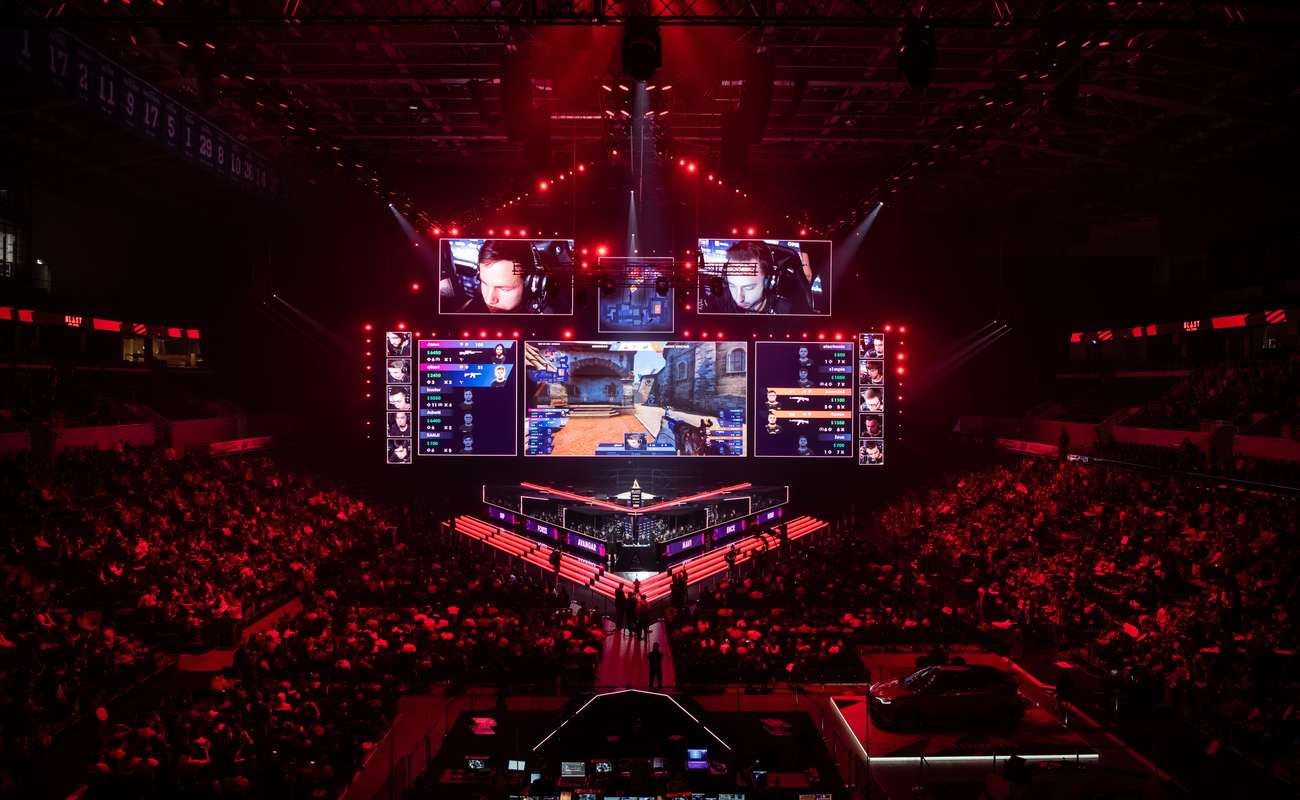 Esports counter strike global offensive match held at Moscow Russia in a packed out arena with red lighting.