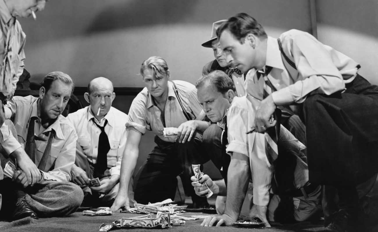 black and white photograph of worker men gambling on the floor