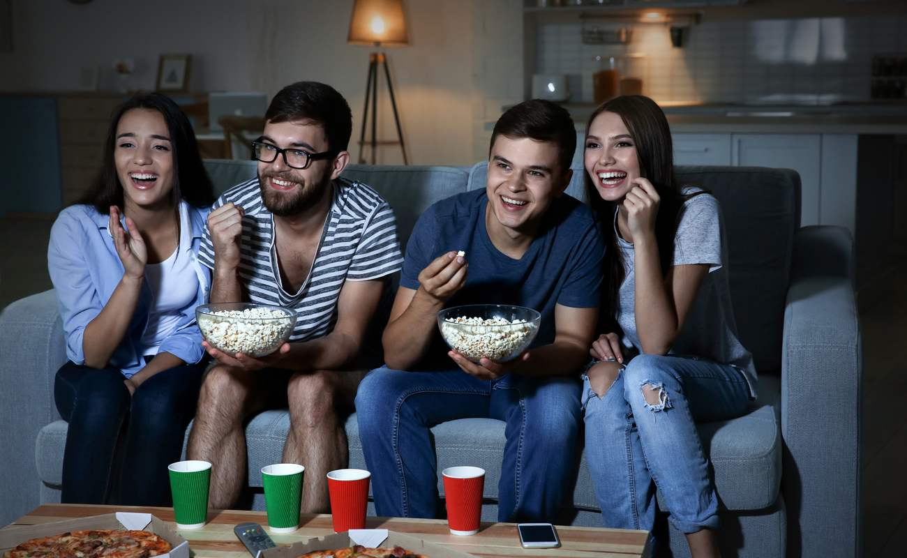 Men and women laughing at a movie whilst eating popcorn