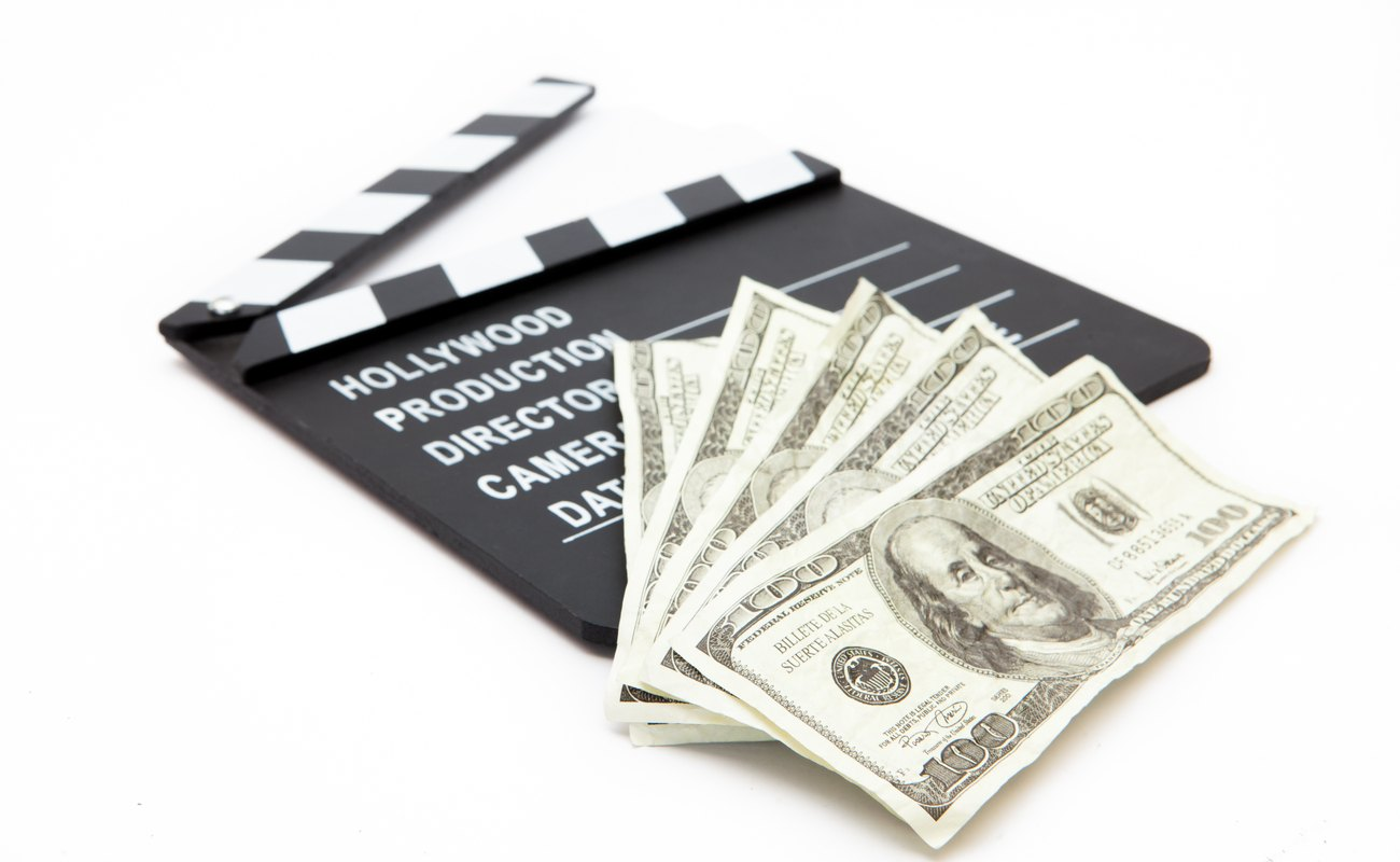 Film slate with 100 dollar bills on top