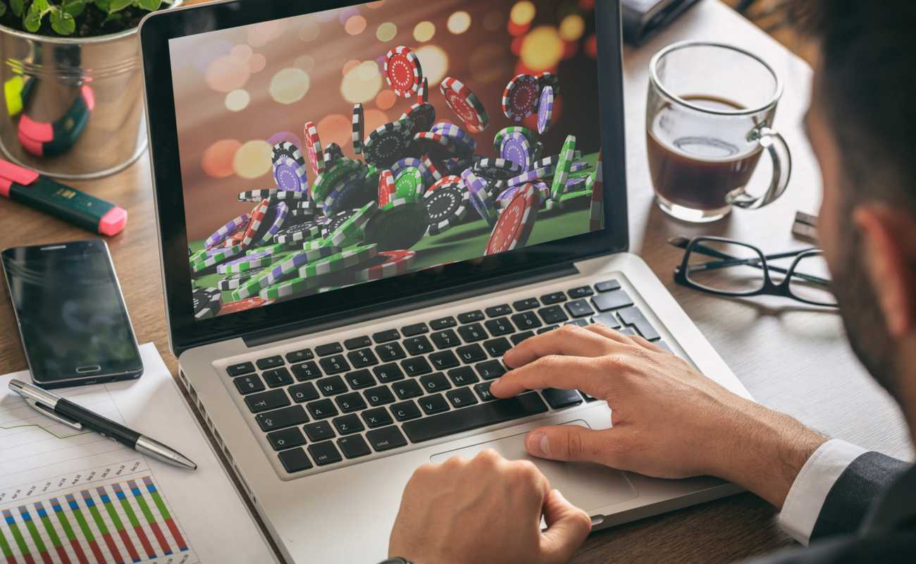 man using laptop with casino chips on screen concept of online gambling