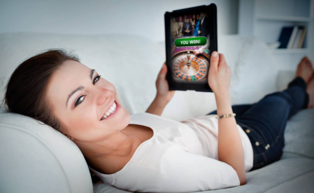 smiling woman lying on couch with tablet showing successful online gambling