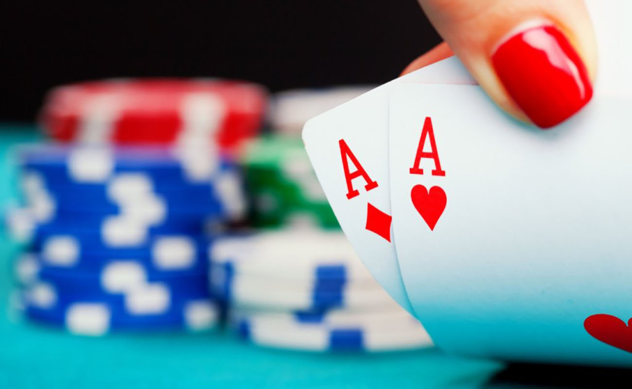 two ace cards with stacks of poker chips in the blurred background