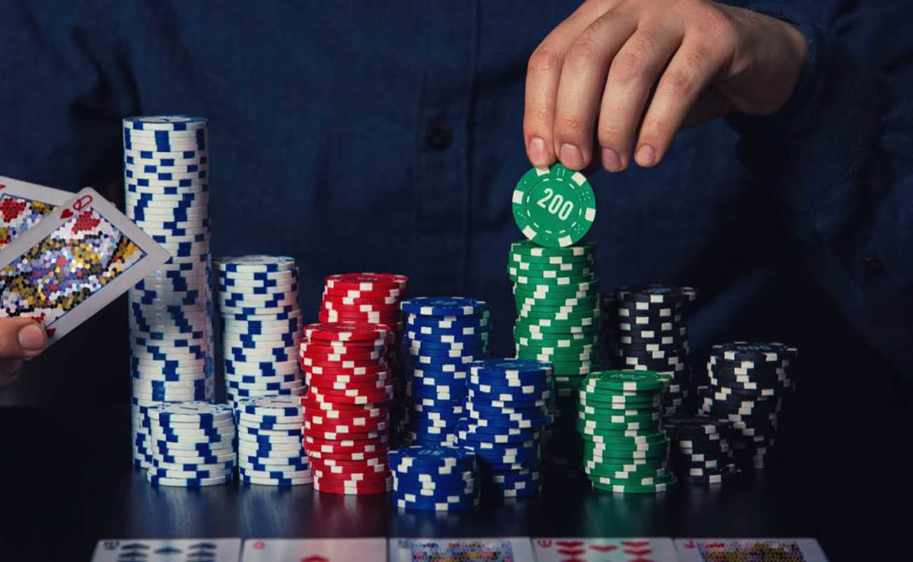 male hand stacking up piles of poker chips