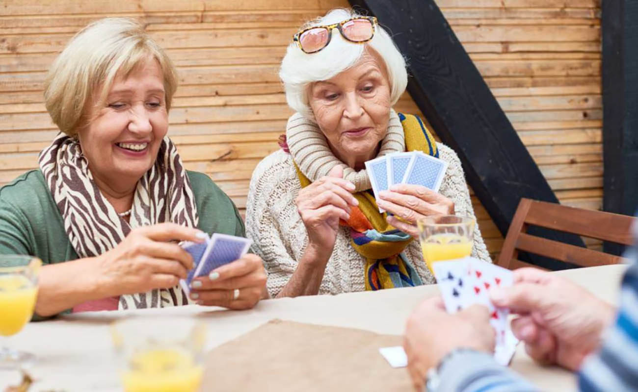 two seniors smiling and player poker