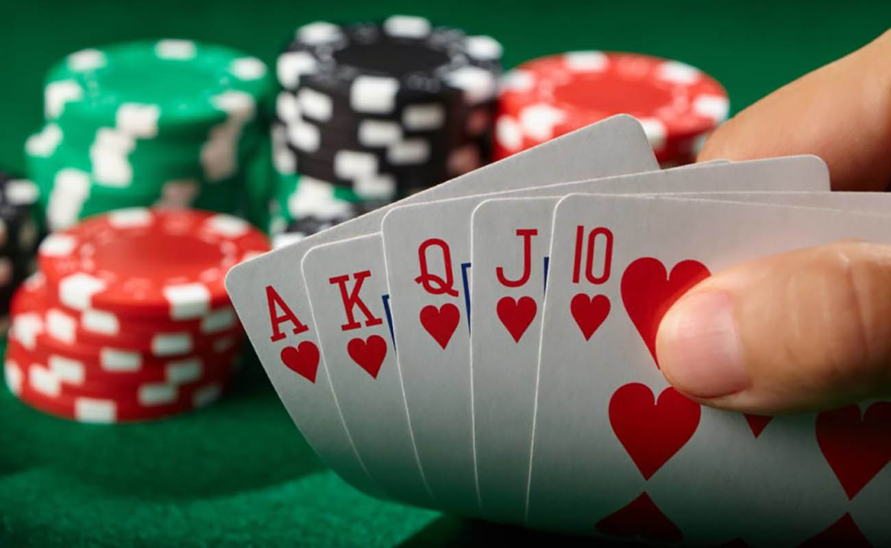 poker player showing a royal flush with casino chips in the background