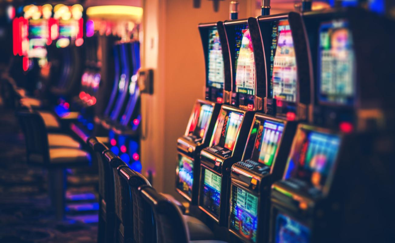 A row of casino slots with lots of different color lights in a dimly lit casino