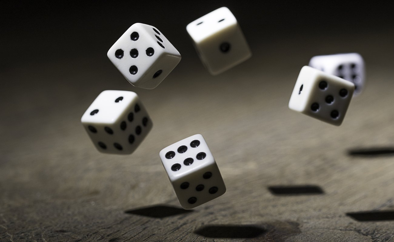 6 white and black dice bouncing in a dark atmosphere on a wooden surface.