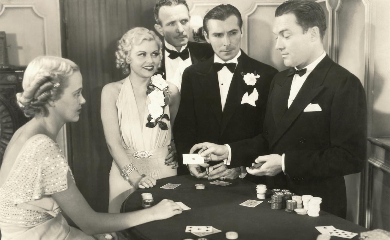 black and white photograph of three men and two women playing poker