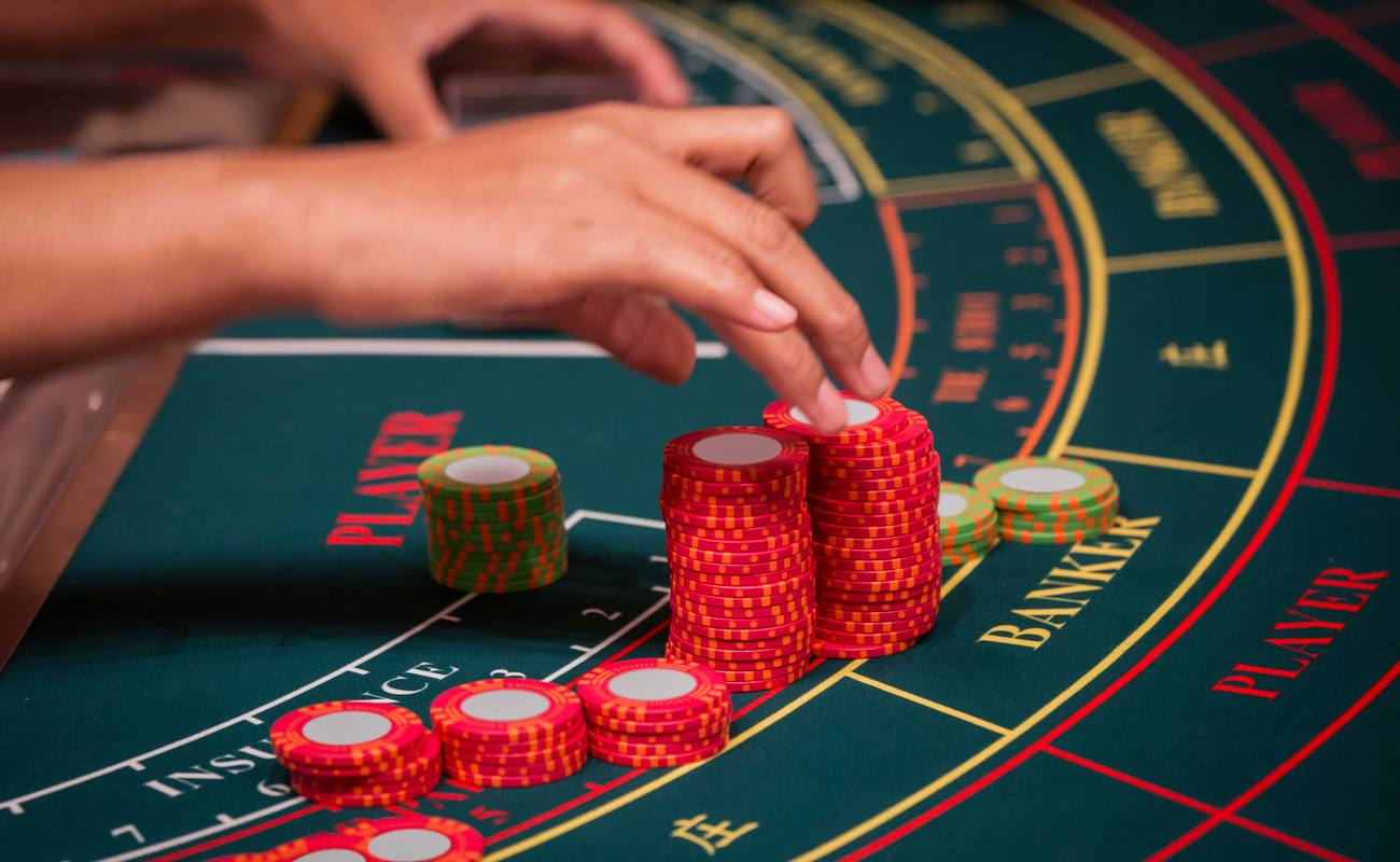 Someone playing baccarat on a green table with red and green poker chip stacks.