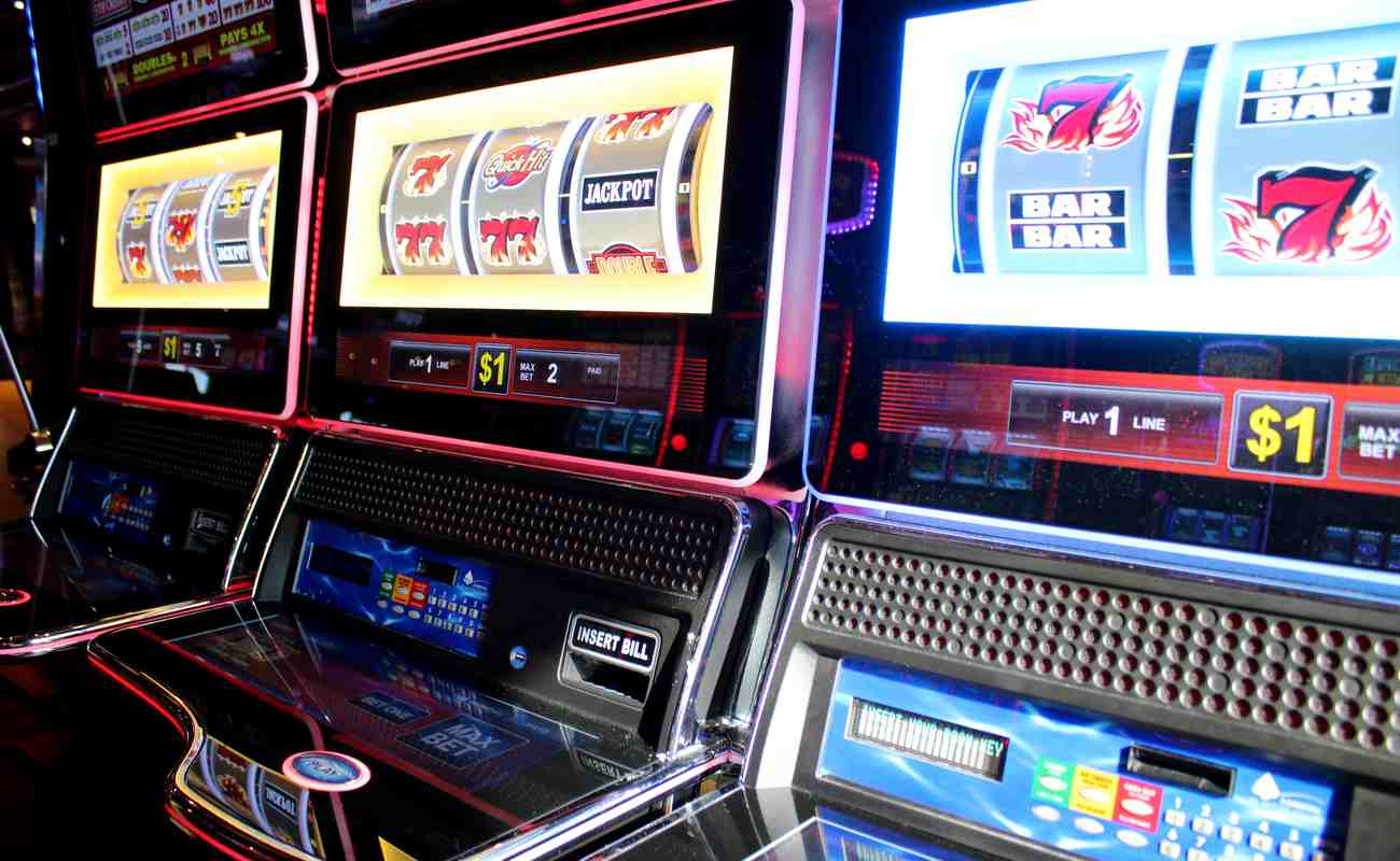 3 casino slot machines, each displaying different jackpot and number combinations on reels.